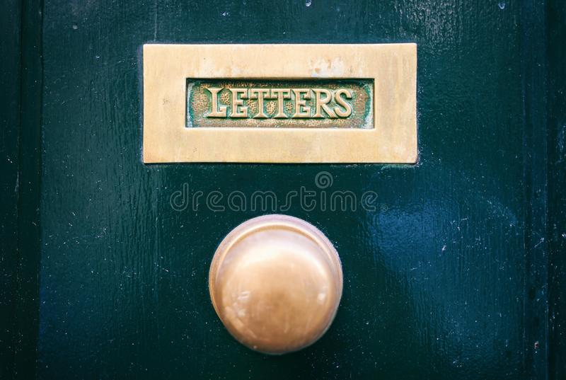 Old brass mail letter box and knob on a green painted front door, text letters stock image