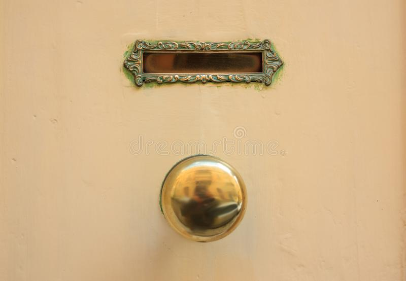 Old brass mail letter box and knob on a yellow painted front door royalty free stock photo