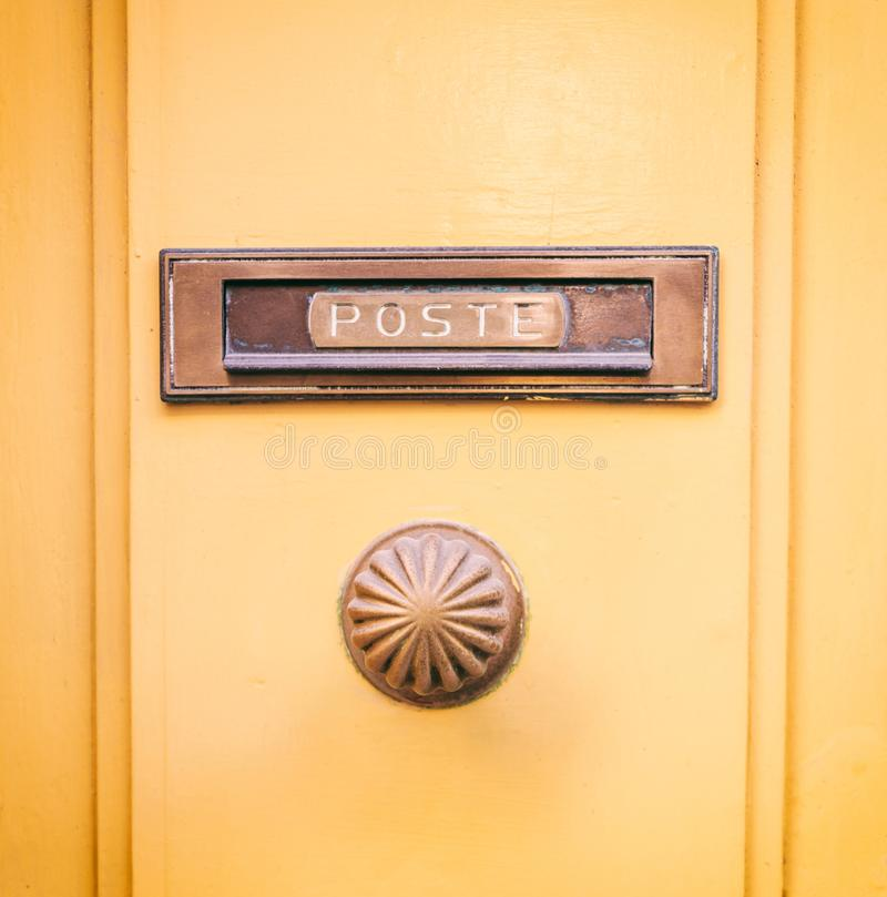 Old brass mail letter box and knob on a yellow painted front door, text poste stock photo