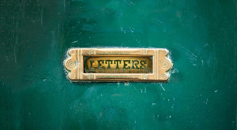 Old mail letter box on a green painted front door, text letters royalty free stock photos