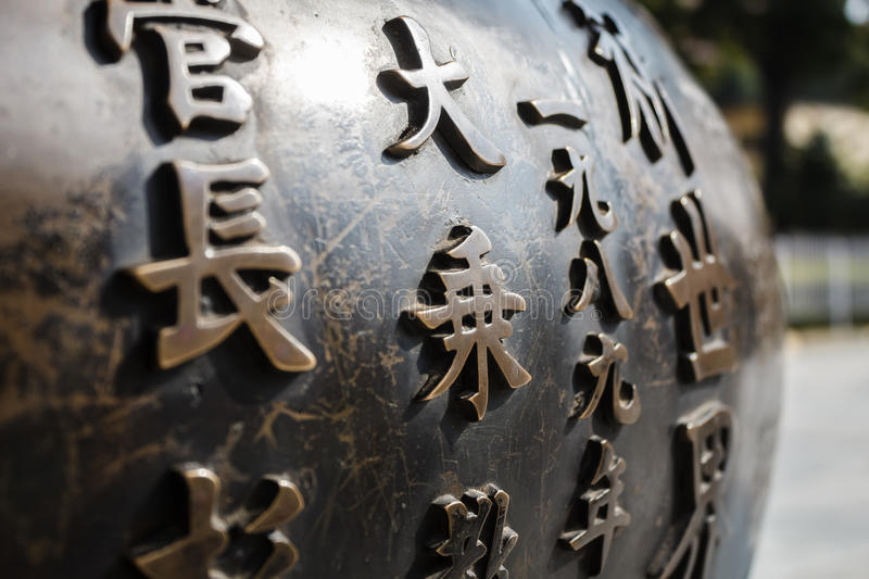 Old brass pot ornated with traditional japanese script. Old brass pot ornated with traditional japanese religious script royalty free stock photography