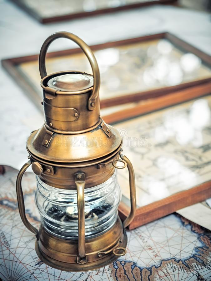Old brassy ship lantern stands on a map of the seas near pictures with the image of sea knots.  royalty free stock image
