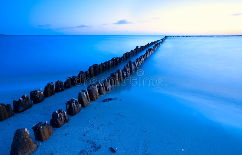 Old breakwater in sea with long exposure royalty free stock photography