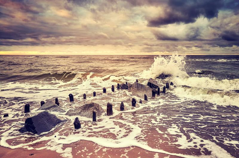 Old breakwater at sunset, color toned picture. Selective focus royalty free stock photos