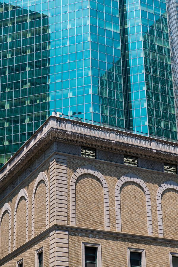 Modern glass and steel skyscraper contrasted with an old brick building with ornate trim and arches. Old brick building contrasted with modern glass and steel royalty free stock photo