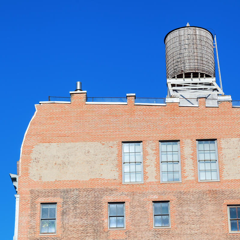 Old brick building in Manhattan, New York City. Industrial brick building with typical water tank on the roof in Manhattan, NYC stock photography