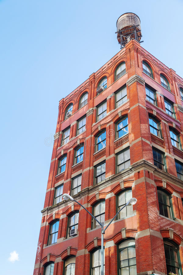 Old brick building in Manhattan, New York City. Industrial brick building with typical water tank on the roof in Manhattan, NYC royalty free stock image