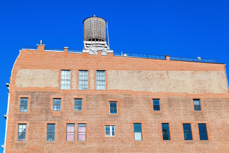 Old brick building in Manhattan, New York City. Industrial brick building with typical water tanks on the roof in Manhattan, NYC royalty free stock photography