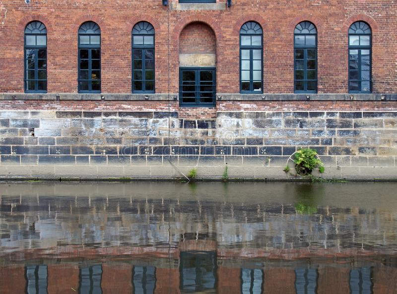 Old brick canal warehouse in leeds with windows reflected in the water. An old brick canal warehouse in leeds with windows reflected in the water stock images