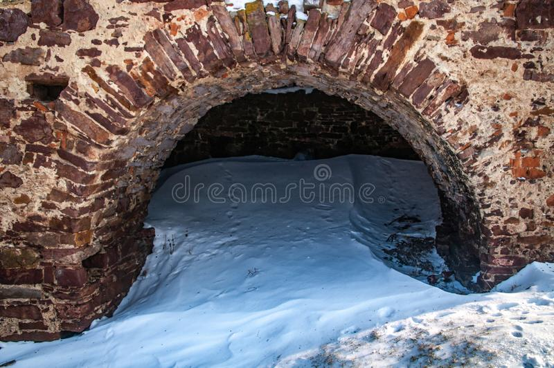 Brick arch of the castle in winter. Old brick castle arch in winter royalty free stock images