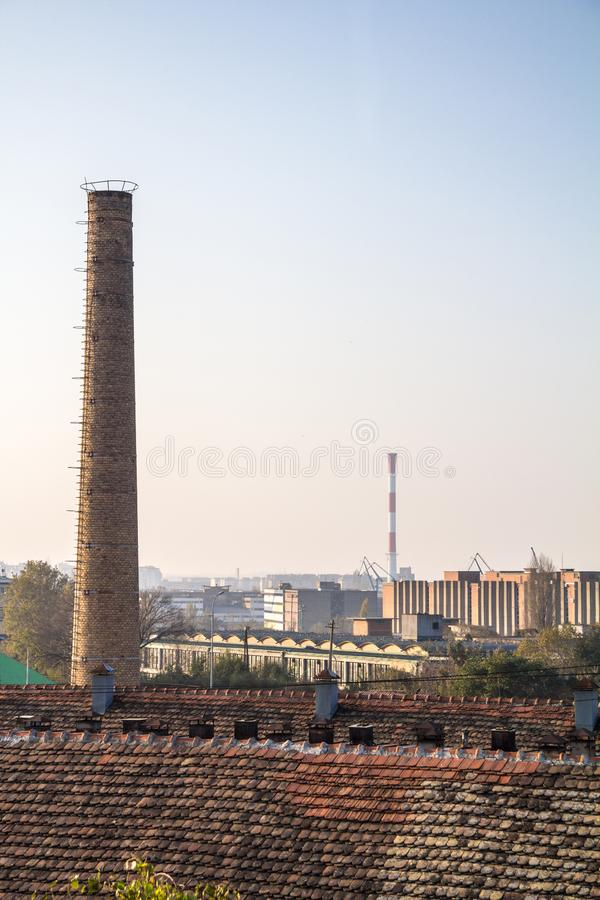Old brick chimney from an abandoned factory, from the industrial revolution, with a more modern industrial zone can be seen. Picture of and old red brick chimney royalty free stock photography