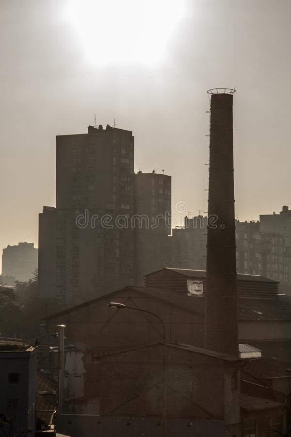 Old brick chimney from an abandoned factory, from the industrial revolution, while an socialist yugoslav housing block building. Picture of and old red brick stock photo