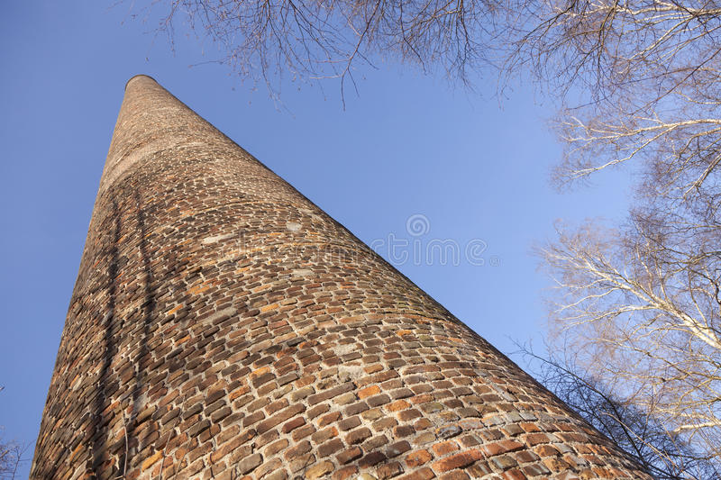 Old brick factory chimney and birch trees under blue sky stock photos