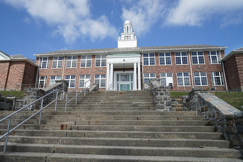 Old brick school. Many concrete steps lead up to the front of an old red brick schoold building.  There is a white cupola on top of the building with a bright stock photography