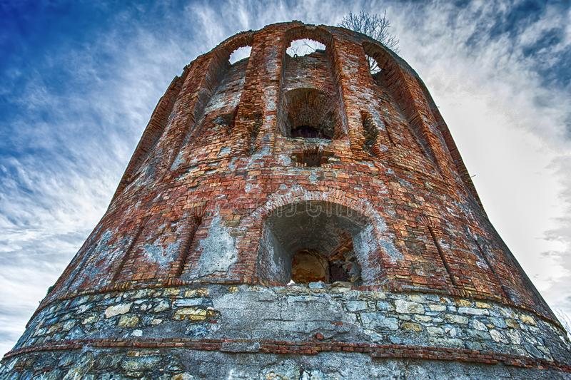 old brick tower under a blue cloudy sky stock photos