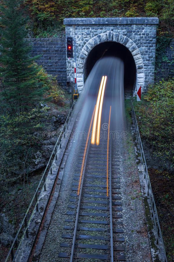 Old brick tunnel in the mountains and incoming train. With long exposure stock images