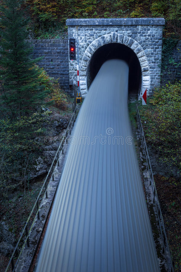 Old brick tunnel in the mountains and incoming train. With long exposure royalty free stock images