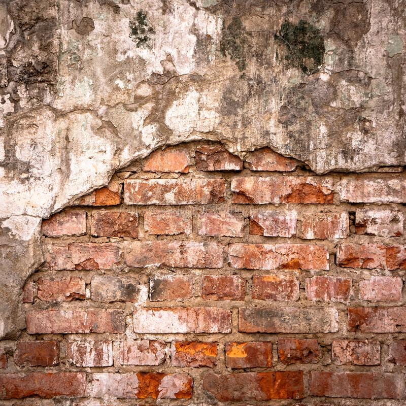 Old brick wall in a background image. Plastered Brickwall With Chipped Stucco Pieces. Red Textured Brick Wall With. Damage Surface. Old Grunge Abstract royalty free stock photo
