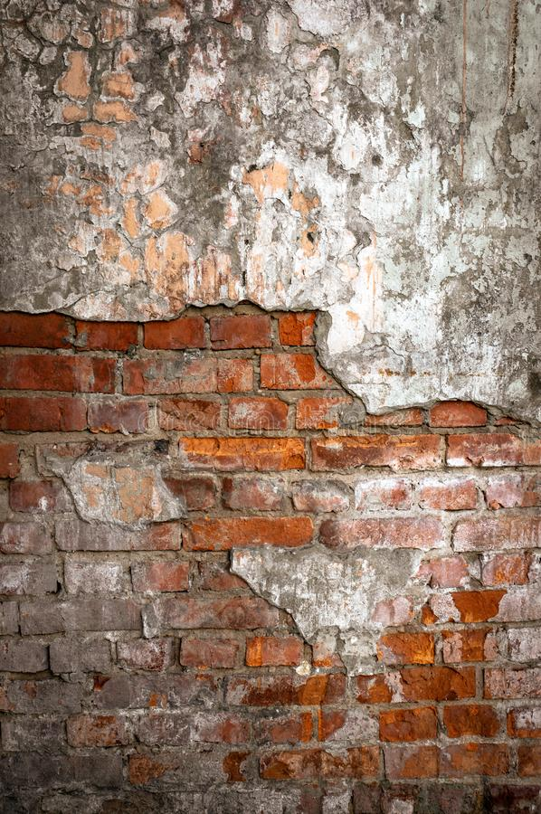 Old brick wall in a background image. Plastered Brickwall With Chipped Stucco Pieces. Red Textured Brick Wall With. Damage Surface. Old Grunge Abstract stock photo