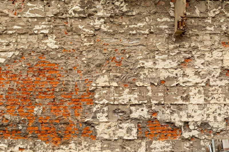 Old brick wall with destroyed plaster and concrete. Dismantling the building stock image