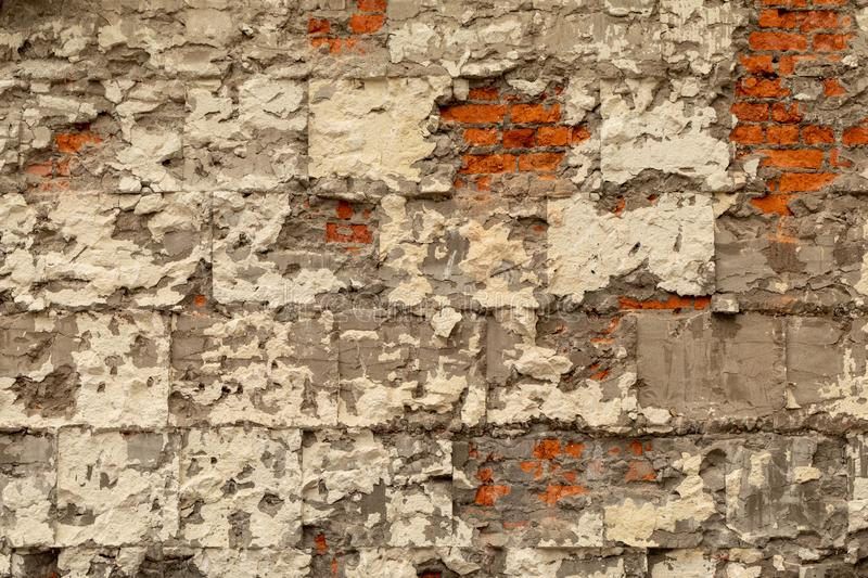 Old brick wall with destroyed plaster and concrete. Dismantling the building stock photo