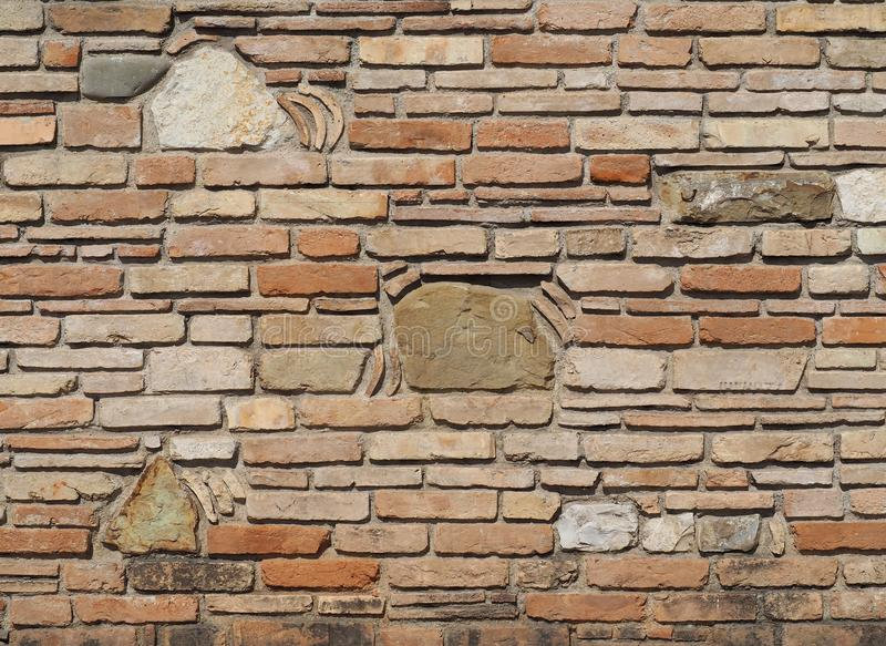 Old brick wall with embedded stones of different sizes and fragments of terracotta roof tiles in the texture stock image