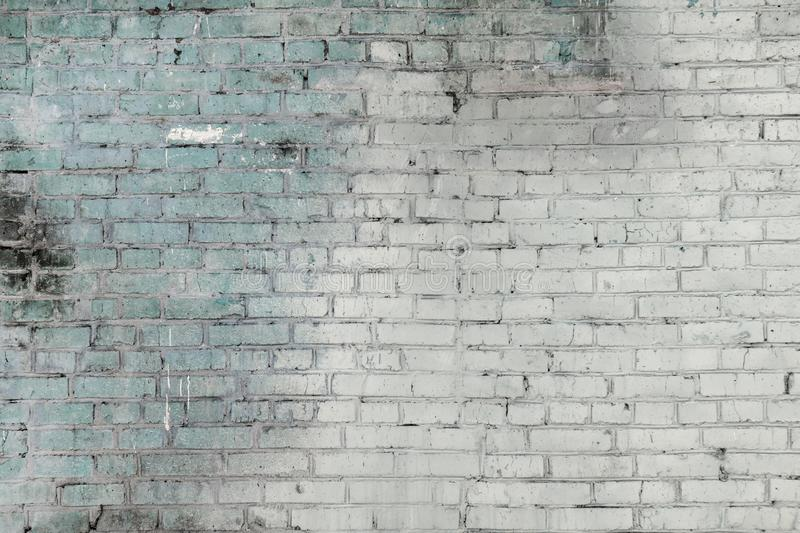 An old brick wall made of gray and green bricks. Empty background of smooth rows of stones. stock images