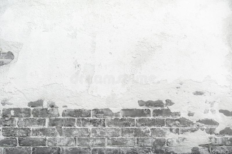 Old brick wall with peeling cracking cement plaster, grunge background stock photo