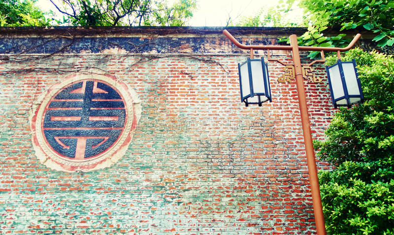 Red old brick wall outdoor lamp garden light landscape lighting. Old brick wall with Chinese pattern. Lamppost, outdoor lamp, garden light lantern beside red stock photo