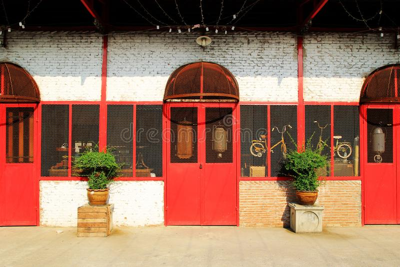 Old brick wall with red doors and windows and two pot plants. stock images