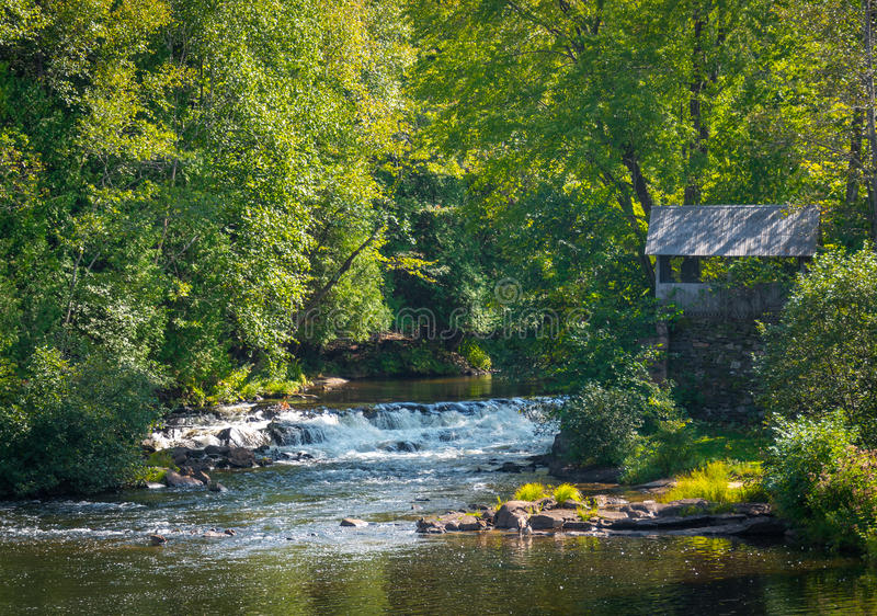 Old brick wall shed, green summer trees. Rapids of babbling water flow in a scenic woodland setting. Old brick wall and watermill shed next to small woodland royalty free stock photos