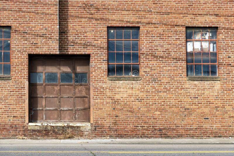 Old Brick Warehouse Door And Windows. Horizontal shot of an old red brick warehouse with door and windows royalty free stock image
