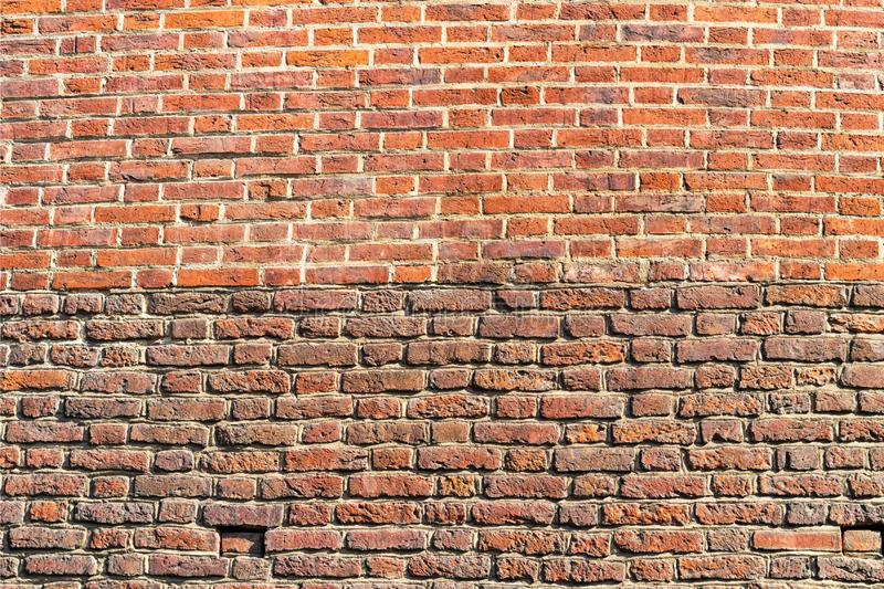 Old brickwork. The wall is made of red brick. The upper part of the wall is a lighter color. The bottom of the wall is darker in. Color royalty free stock images