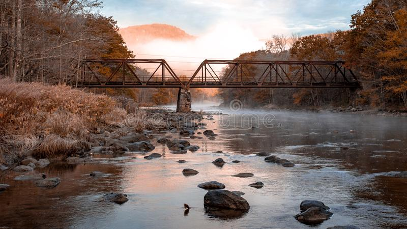 Old bridge crossing the river. A old metal and wood bridge crossing the river on a fall morning royalty free stock photography