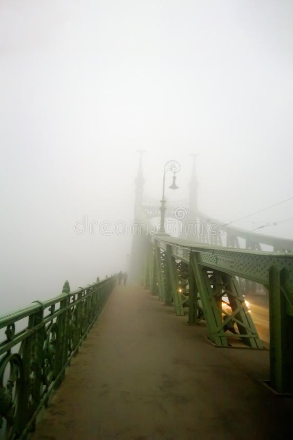 Old bridge in the fog. Mystical vision. A couple of people walk together in the fog. stock photo