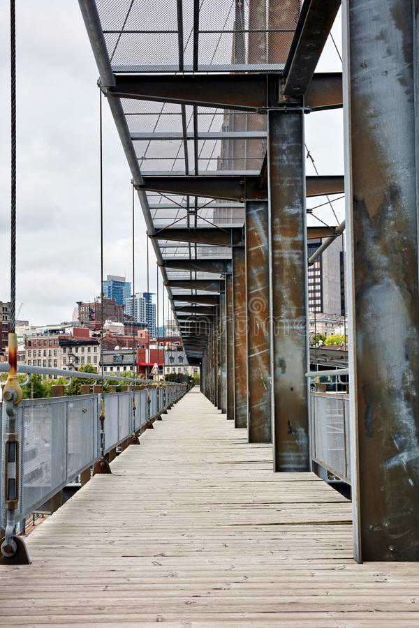 Old bridge made of wooden plank floorboard and metal steel girder. In the city stock photos