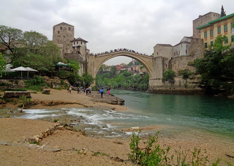 The Old Bridge with many tourist over the Neretva River in the Historic Town of Mostar, Bosnia and Herzegovina, May 1st, 2016 royalty free stock photography