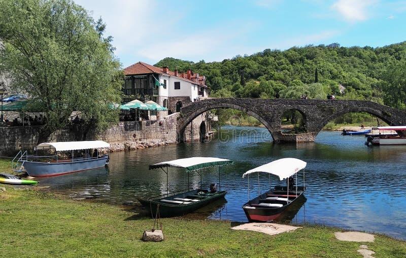 Old Bridge over Crnojevica river, Rijeka Crnojevica, and the tourist area near the bridge, Montenegro royalty free stock photo