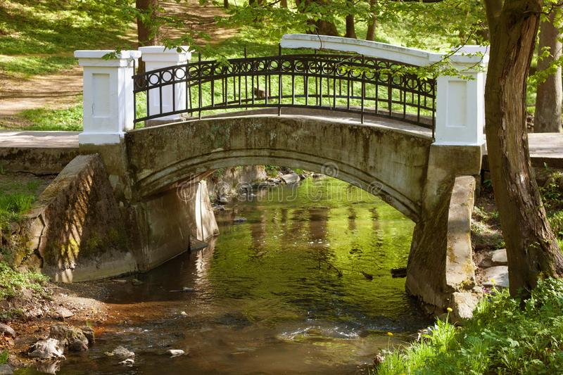 Old bridge over the river in Kaliningrad Central Park. In early spring. Russia.The park was known as Luisenwahl while part of Konigsberg, Germany, until 1945 royalty free stock image