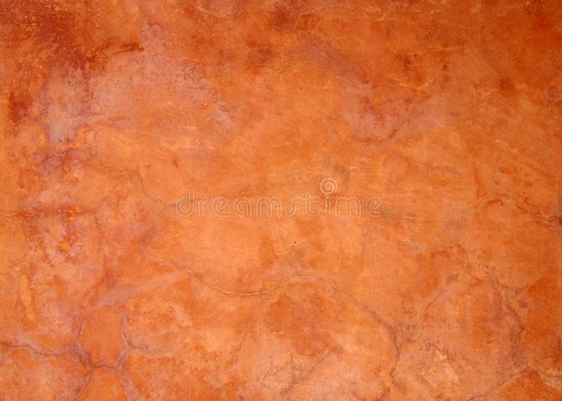 Old bright orange brown painted faded stained cracked rough plaster wall background. An old bright orange brown painted faded stained cracked rough plaster wall royalty free stock image