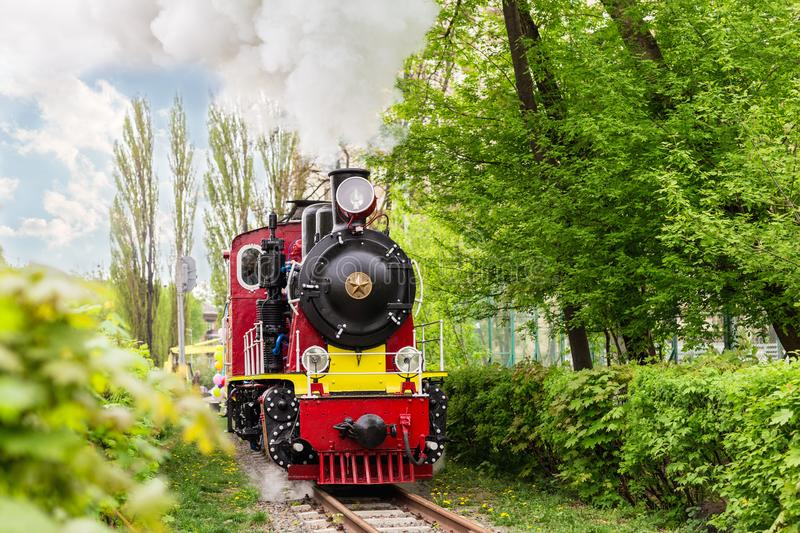 Old bright train in green city park on touristic railroad. Retro locomotive with clouds of steam from smoke pipe in forest royalty free stock images