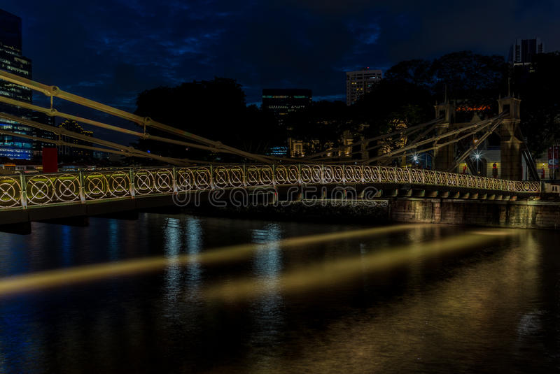 Old brightly illuminated bridge on the Singapore river at sunset royalty free stock photos