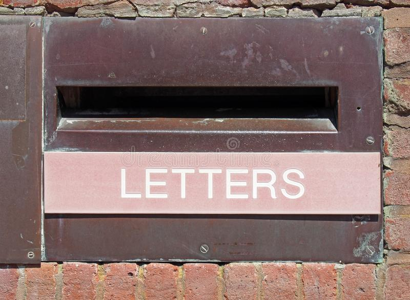 Old british postal mail box in a brick wall with rusted metal surround and the word letters on a faded red panel stock images