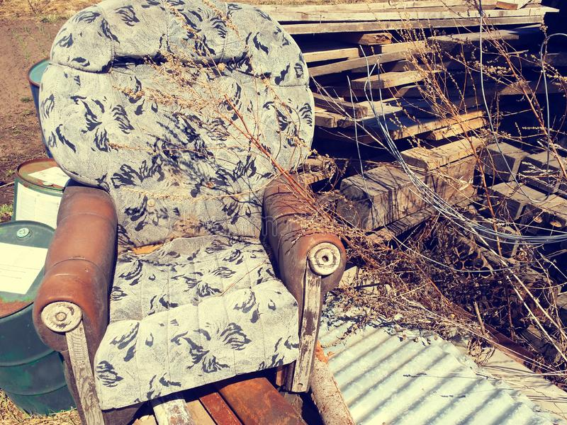 Old broken armchair at the dump with boards. Old dirty brown broken armchair at the dump with boards, barrels and rusty pipes. Vintage style, torn, garbage stock photography