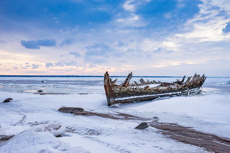 Old broken boat wreck and rocky beach in wintertime. Frozen sea, evening light and icy weather on shore like fairy tale country. Winter on coast. Blue sky stock photo