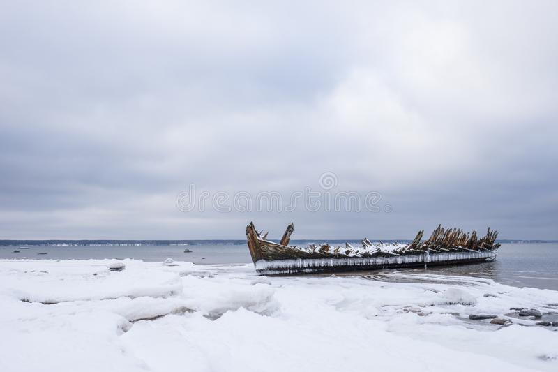 Old broken boat wreck and rocky beach in wintertime. Frozen sea, evening light and icy weather on shore like fairy tale country stock images