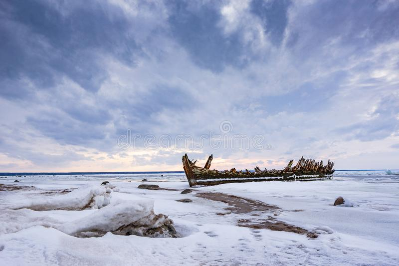 Old broken boat wreck and rocky beach in wintertime. Frozen sea, evening light and icy weather on shore like fairy tale country. Winter on coast. Blue sky stock image
