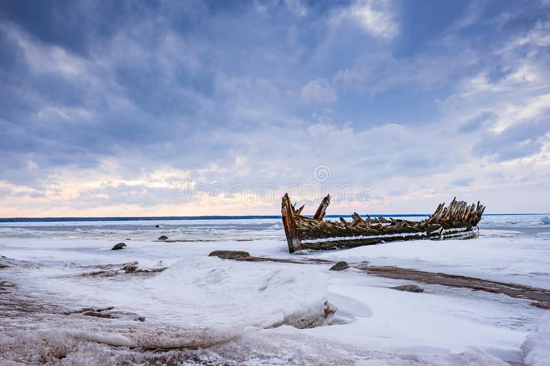 Old broken boat wreck and rocky beach in wintertime. Frozen sea, evening light and icy weather on shore like fairy tale country. Winter on coast. Blue sky royalty free stock photography