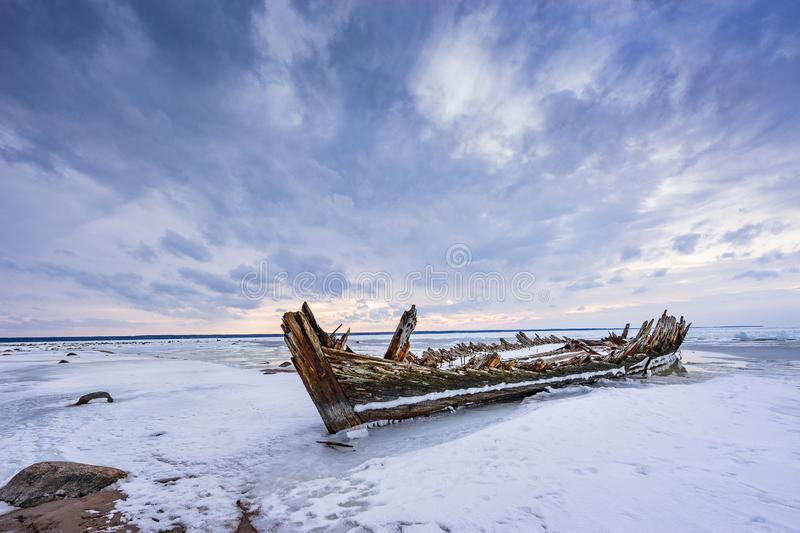 Old broken boat wreck and rocky beach in wintertime. Frozen sea, evening light and icy weather on shore like fairy tale country. Winter on coast. Blue sky stock photos