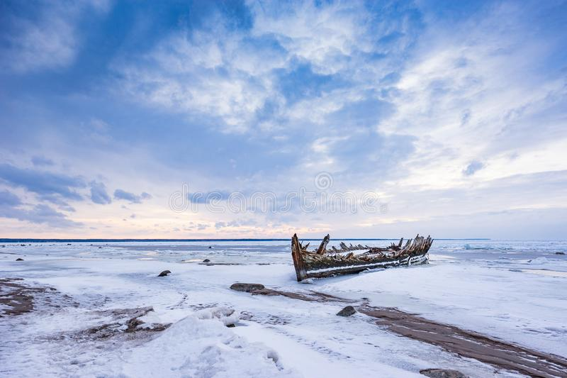 Old broken boat wreck and rocky beach in wintertime. Frozen sea, evening light and icy weather on shore like fairy tale country. Winter on coast. Blue sky royalty free stock images